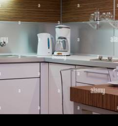 modern white interior kitchen design corner with electrical appliances table chair mug sink and cupboard  [ 1300 x 959 Pixel ]