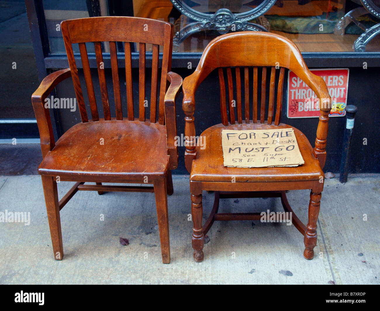 old wood chairs harvest table two wooden on a city sidewalk holding handwritten stock cardboard for sale sign