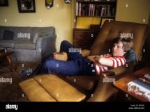 Young White Teen Boy Rests In Large Recliner Chair With
