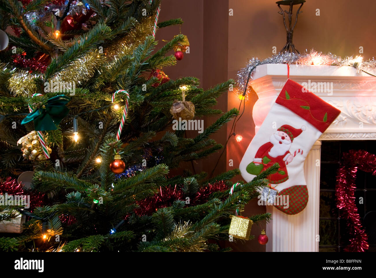 Close Up On Christmas Tree And Stocking Hanging On Fireplace Stock Mantlepiece Decorated For Christmas Stock Photos