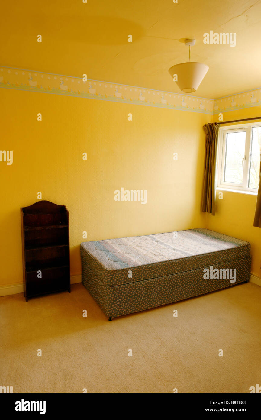 An Empty Bedroom With Yellow Walls And Empty Bed In The Corner Under Stock Photo Alamy