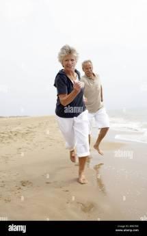 Senior Couple Barefoot Cheerfully Running Sandy