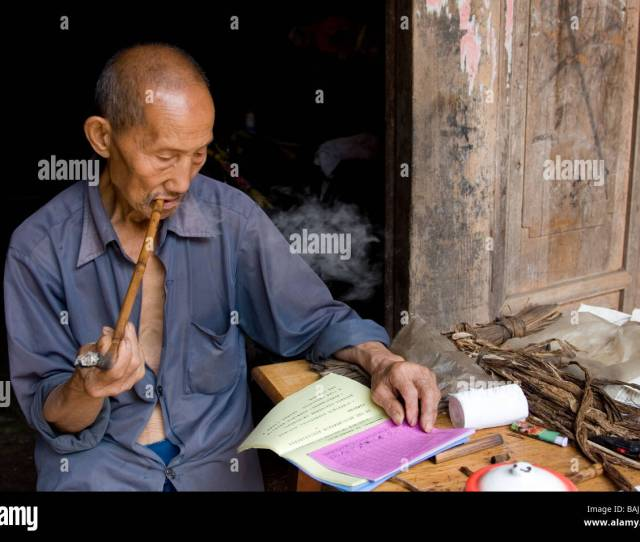 An Old Man In The Courtyard Of His Farmhouse Smoking Home Made Pipe And Reading Chinese Horoscope Material In Small Village