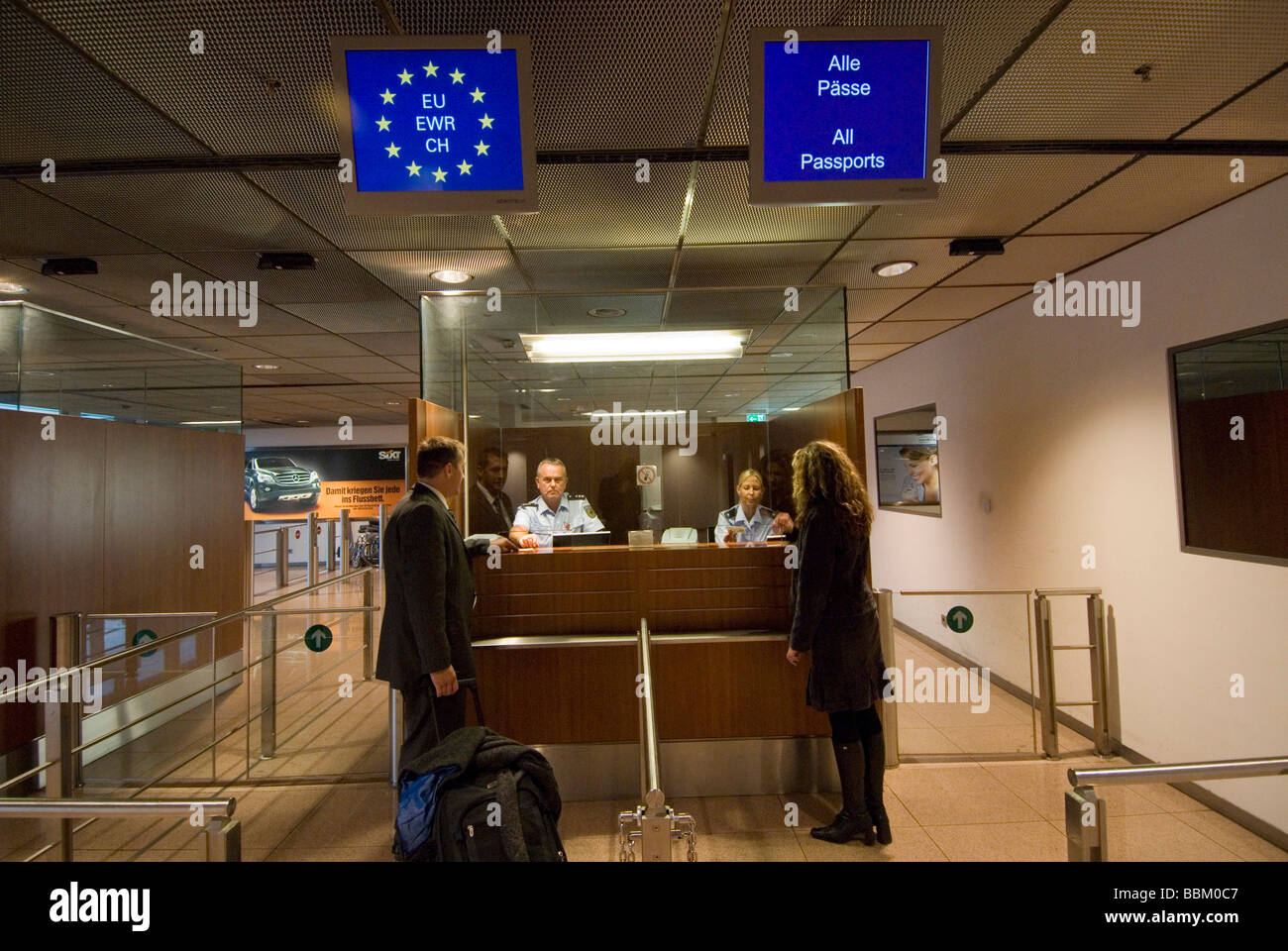 Passport control security officers security checks man woman Stock Photo Royalty Free Image