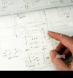 man referring to electrical wiring diagram stock image [ 1300 x 956 Pixel ]