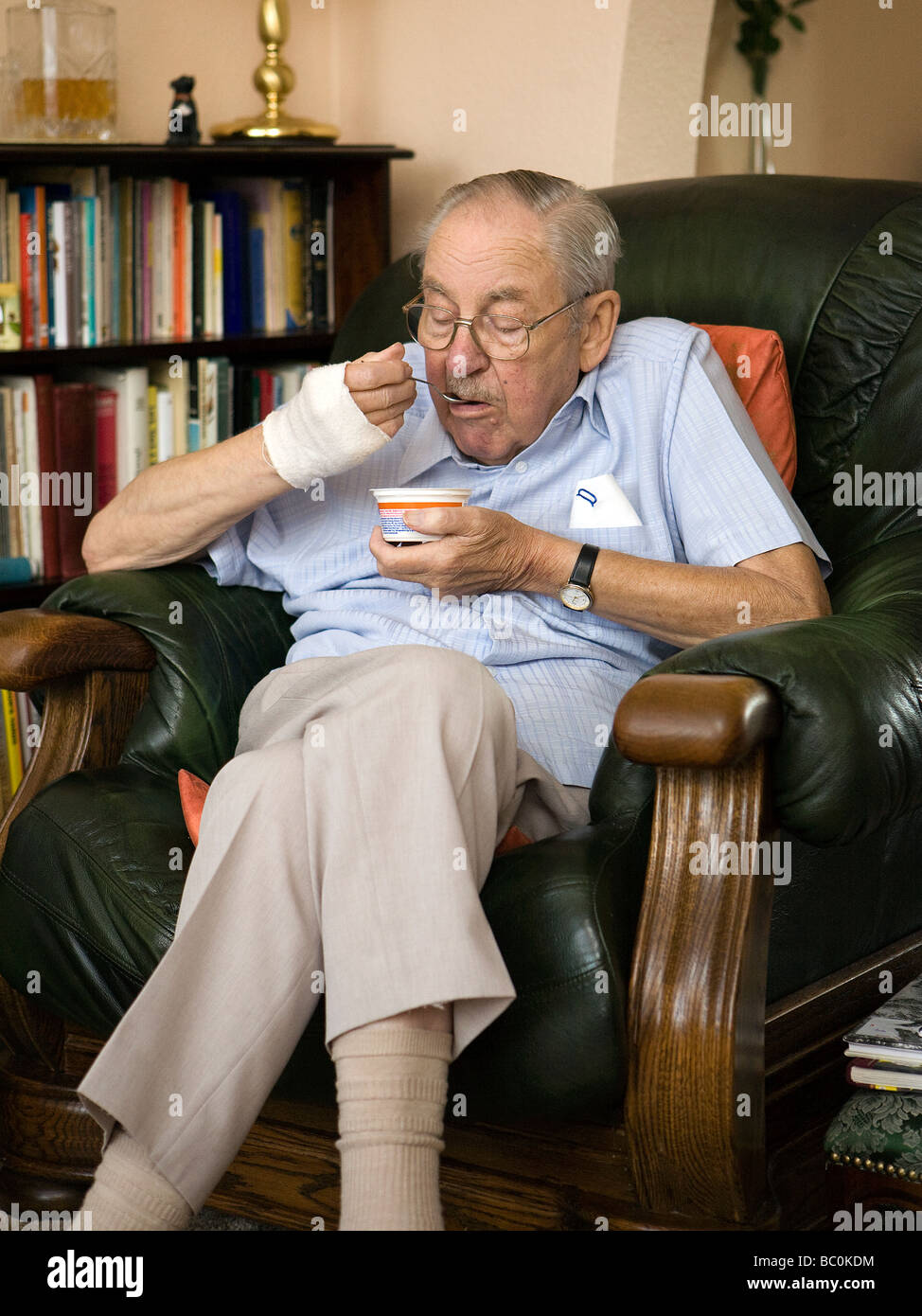 Old man sits in his favourite armchair eating a yoghurt