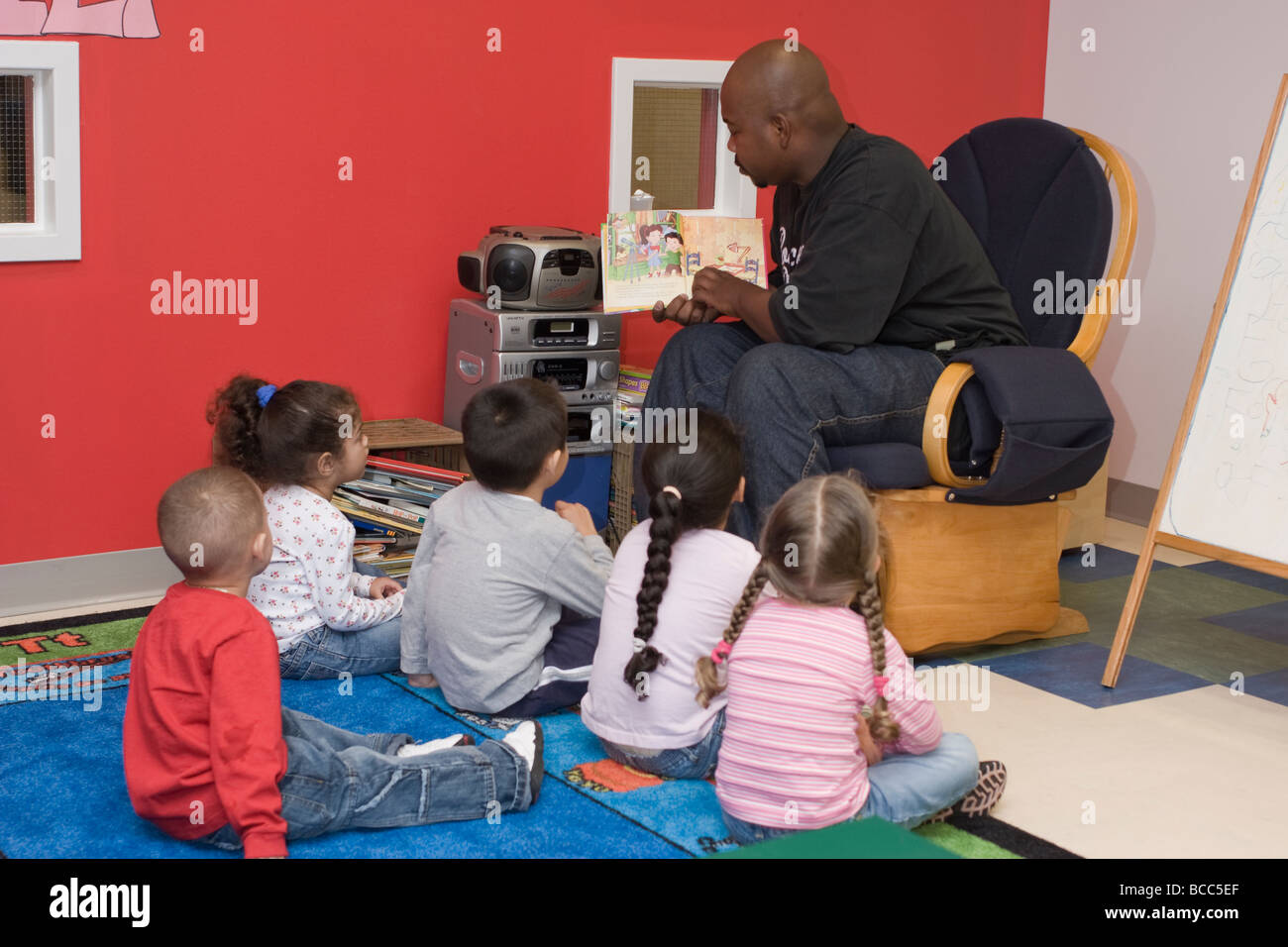 African American Male Preschool Teacher Reading A Book To