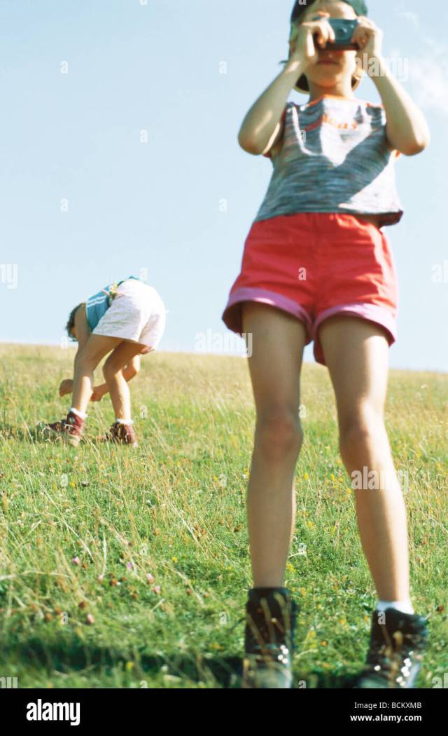 Girl Taking Photo Second Child Bending Over Looking At Grass In Background