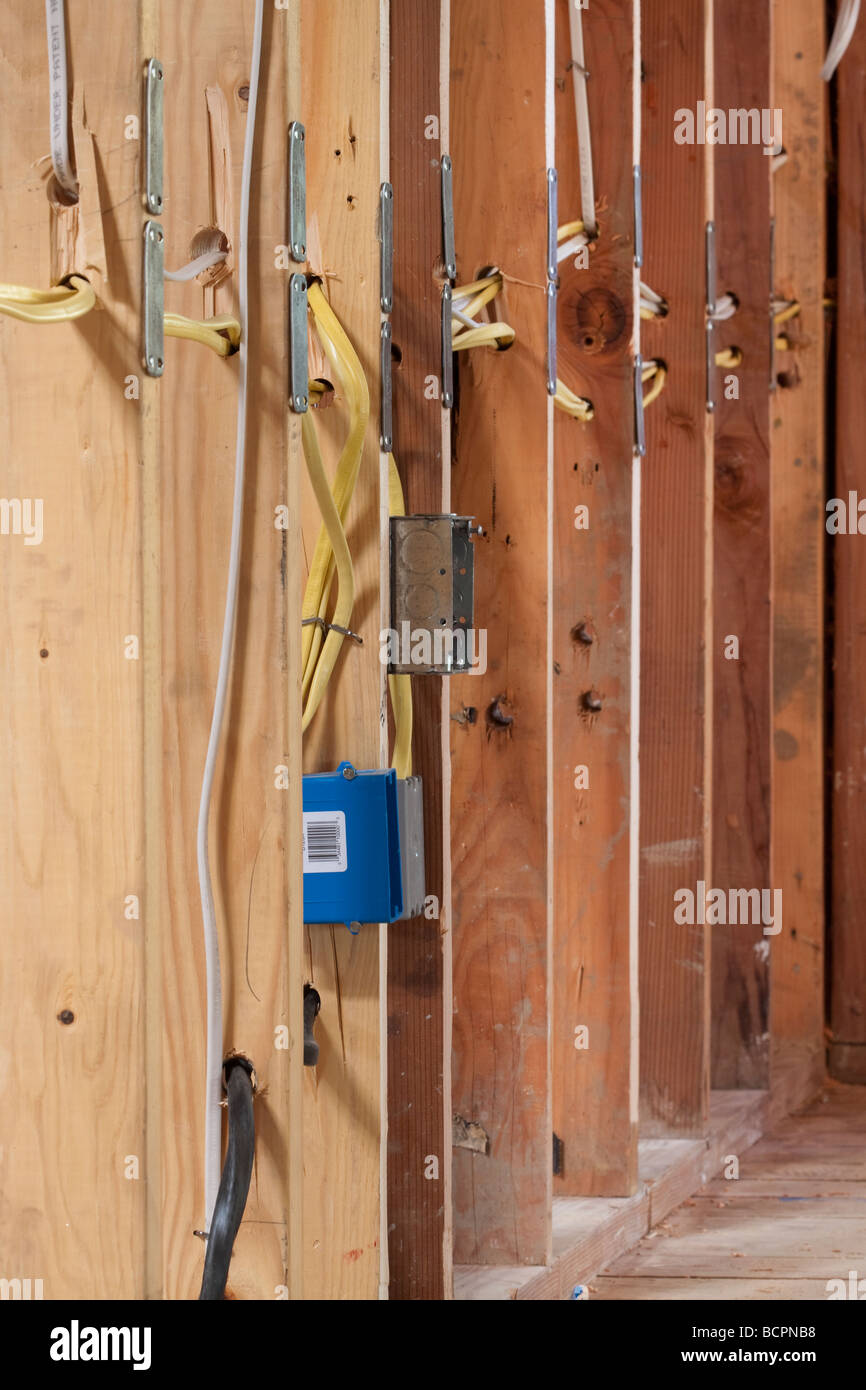 medium resolution of many electrical wires running through wall studs and connecting to a metal outlet box at residential construction site