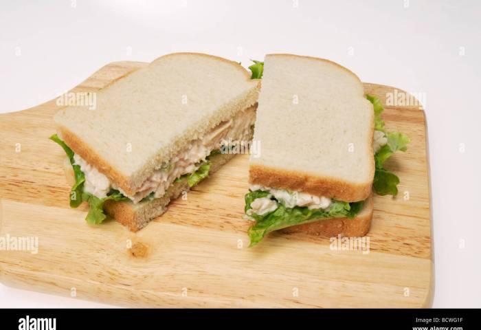 Tuna Mayo Sandwich On White Bread With Lettuce On Wood Cutting Board