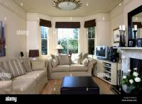 Beige sofas in cream living room with black blinds on bay ...