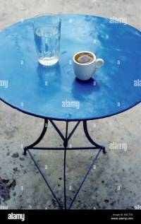 Blue iron table with coffee cup and water glass, Greek ...