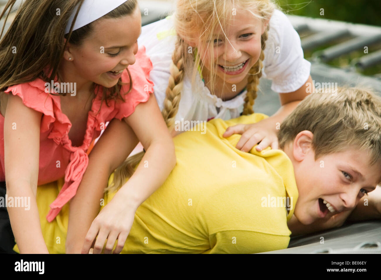 2 Young Girls Wrestling With Young Boy Stock Photo