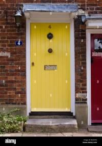 Yellow front door in a row of Victorian terraced houses ...