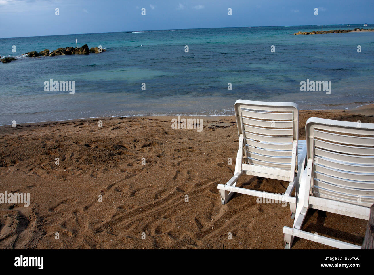 Beach Lounge Chairs Empty Beach Lounge Chairs On The Sand By A Calm Sea Stock Photo