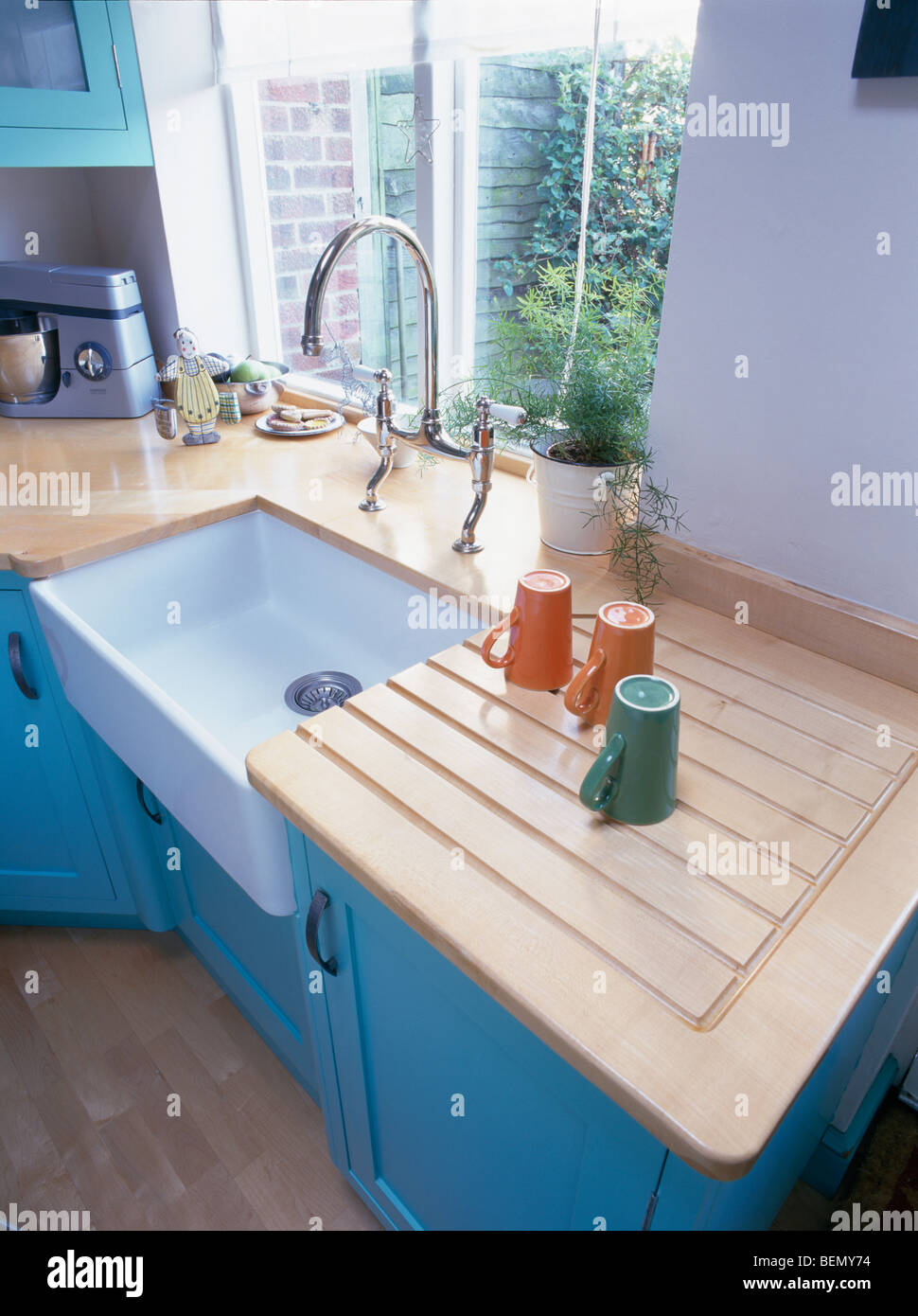 kitchen draining board sink and faucet close up of cups on wooden beside white ceramic in pale turquoise