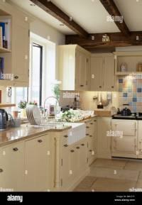 Belfast sink below window in country cottage kitchen with ...