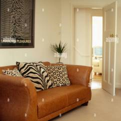 Modern Brown Leather Sofa Reclining Brands Tiger And Leopard Print Cushions On In Cream Living Room
