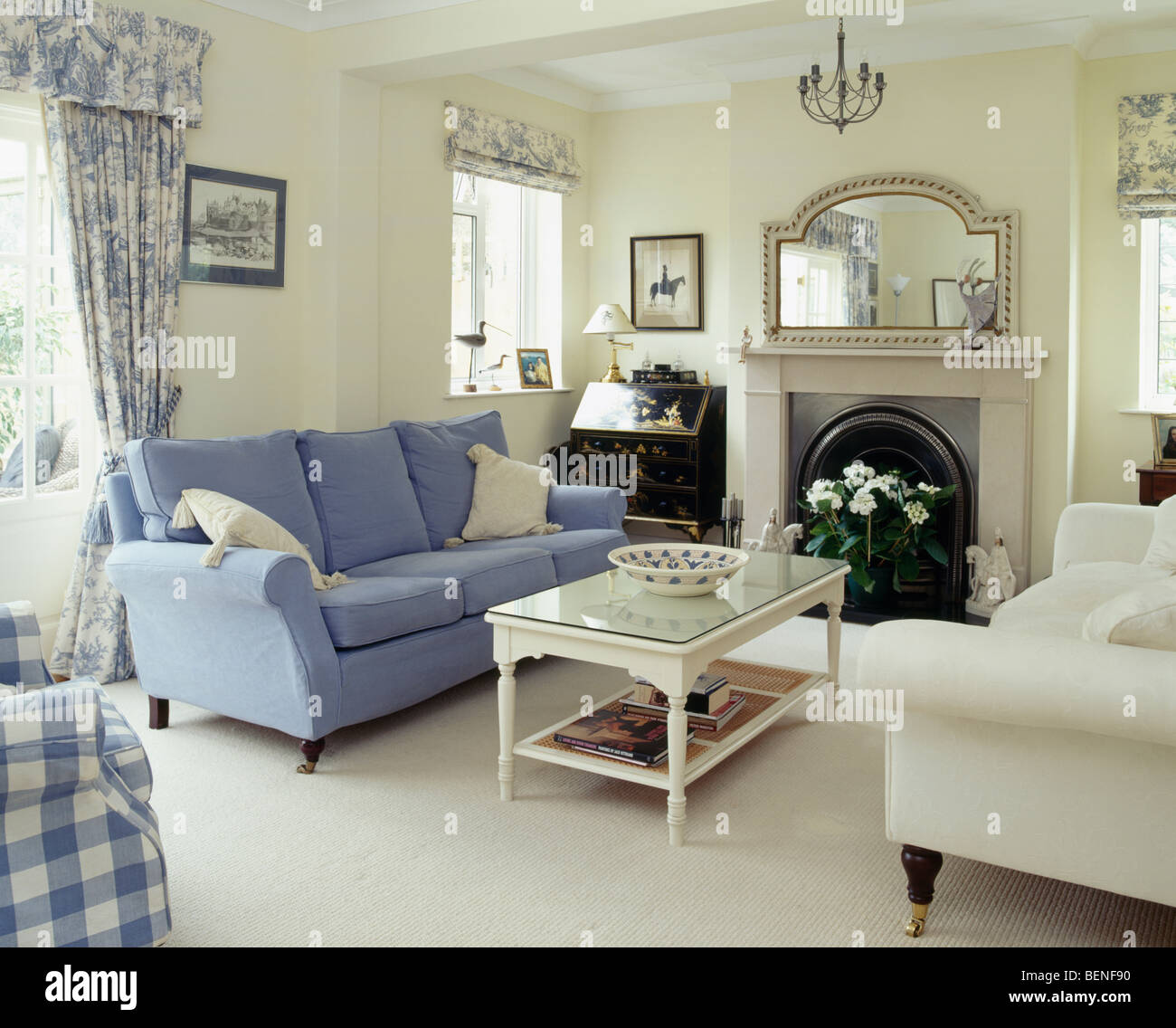 Blue and cream sofas on either side of fireplace in cream