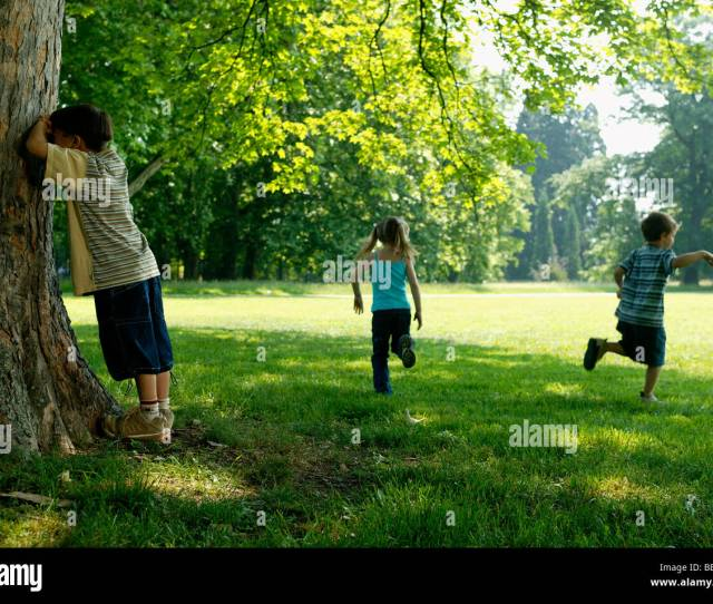 Three Children Playing Hide And Seek In The Park