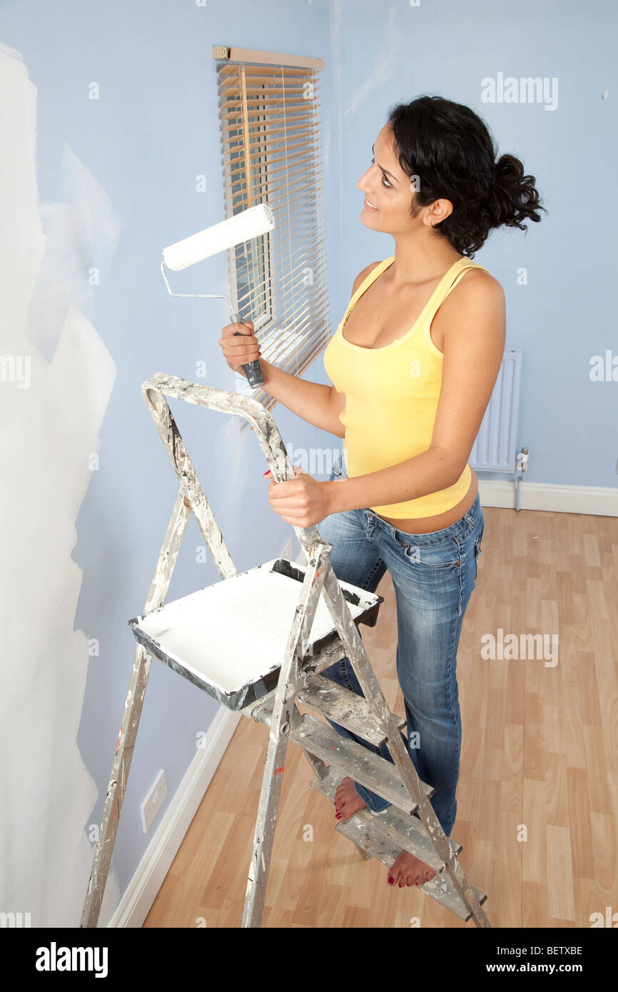 Young dark haired woman painting walls standing on a step
