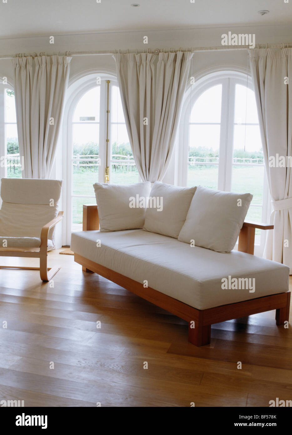 Day Bed With White Cushions In Living Room With Wooden