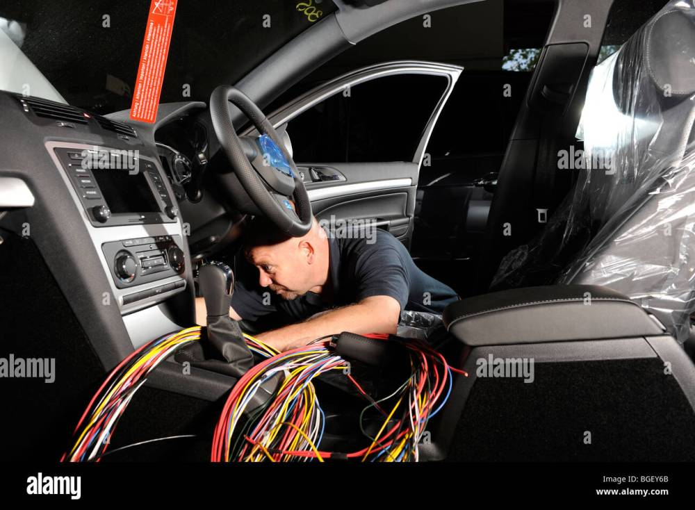medium resolution of a fitter putting a wiring loom harness in a 2009 skoda octavia police car