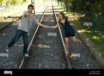 Young Couple Walking Rail Track Holding Hands Stock