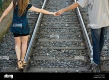 Couple Walking On Railroad Tracks