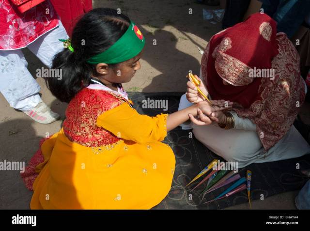 Two Ittle Girls Applying Henna At The Baishakhi Mela In Stock Image