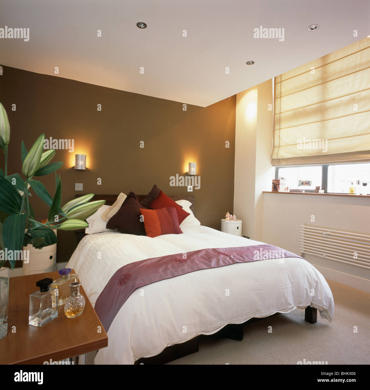 Wall Lights On Brown Wall Above Bed With White Duvet In Modern Stock Photo Alamy