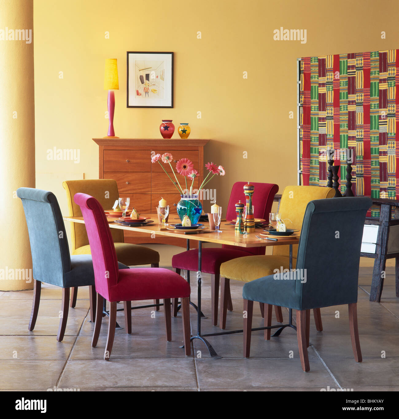 yellow upholstered dining chairs parsons chair cover pattern pink turquoise and blue velour at table in modern room with multi colored screen
