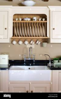 Fitted plate rack in fitted cream cupboard above white ...