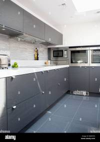 Grey ceramic floor tiles in modern white kitchen with dark