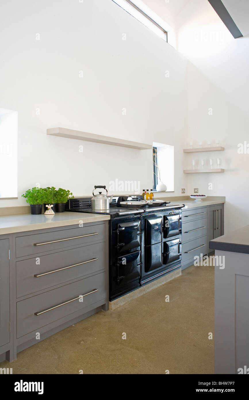 black aga oven in large modern white kitchen with fitted gray units