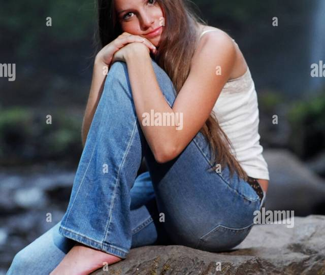 Barefoot Teenage Girl Sitting On A Rock While Looking At The Viewer