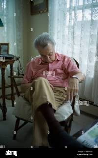 Old man sleeping in living room chair Stock Photo ...