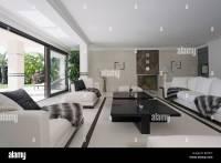 Black+white throws on white sofas in large modern white