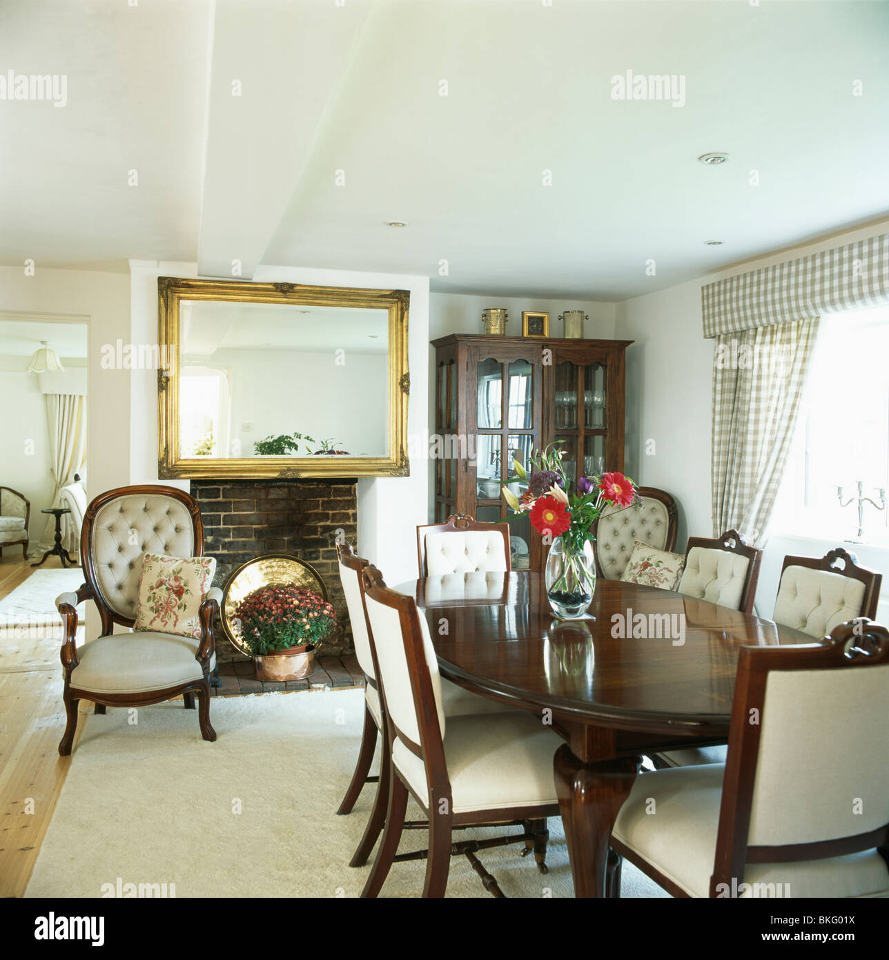 cream upholstered dining chairs rustic office and antique table in white country room with large gilt mirror above fireplace