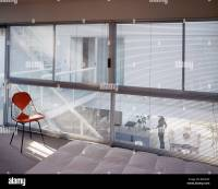 Charles Eames chair in front of glass wall with blinds in ...
