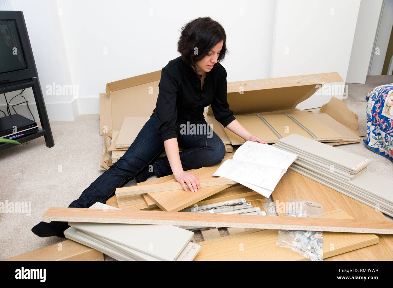 flat pack sofas uk wooden sofa legs online india woman assembling ikea furniture england stock photo