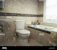 Toilet beside bath with tiled surround in modern beige ...