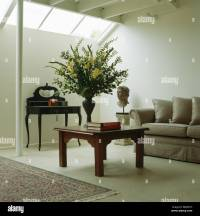 Large flower arrangement on wooden coffee table and beige ...