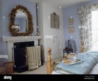 Dried flower garland around mirror above fireplace in ...