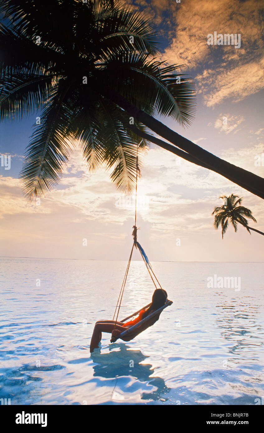 Woman in swing chair hanging from palm tree on Meeru