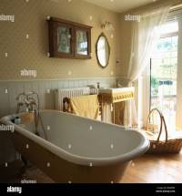 Patterned wallpaper and roll-top bath in traditional ...