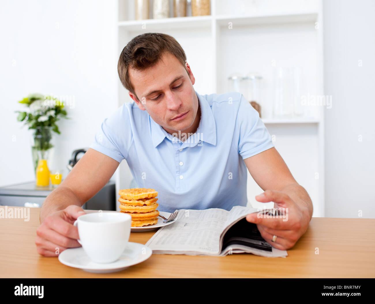Concentrated Man Reading A Newspaper While Having