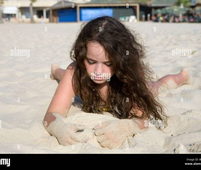Girl Lying On Her Front On The Beach Playing By Herself In The Sand