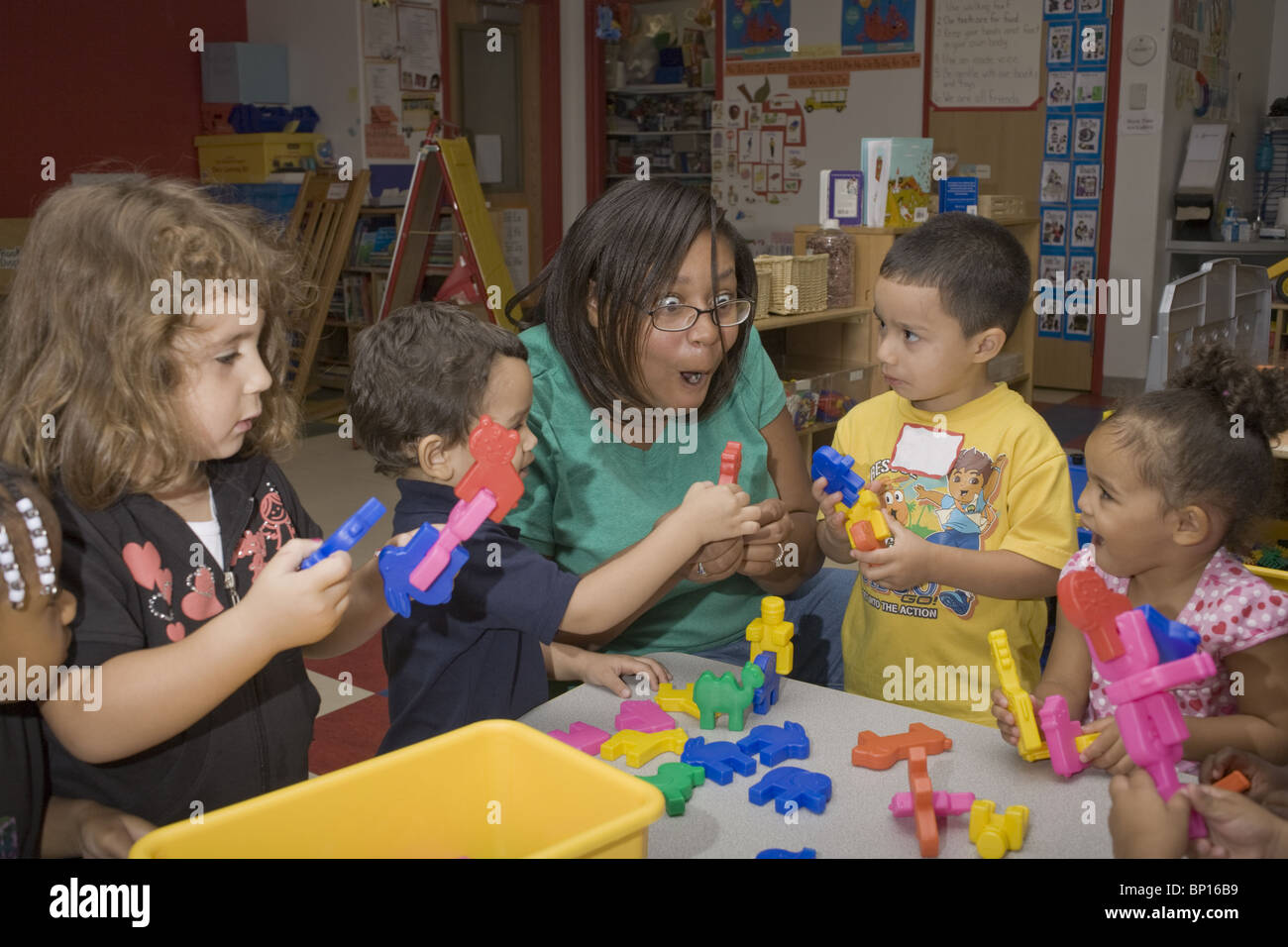 African American Preschool Teacher And Students In The