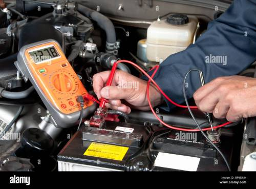 small resolution of an auto mechanic uses a multimeter voltmeter to check the voltage level in a car battery